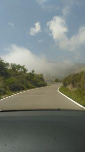 A view of the lovely smooth road winding its way through the mountains and up into the clouds.