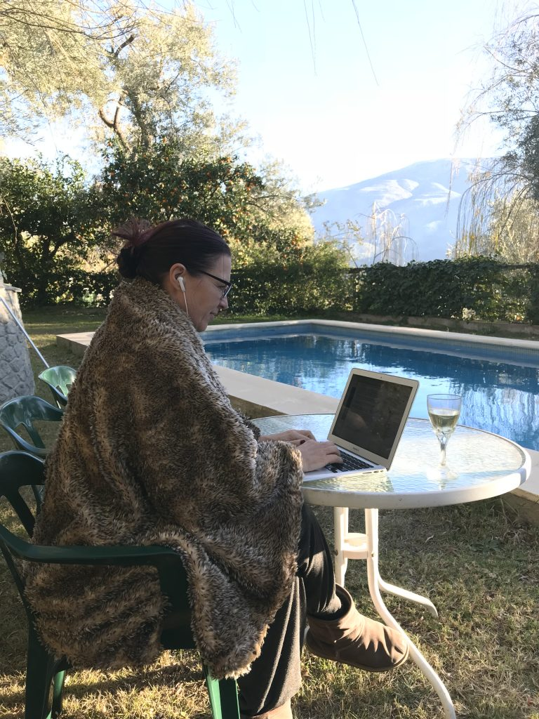 Blogger at work with a glass of obligatory New Year bubbles and a wrap against the chilly mountain air.